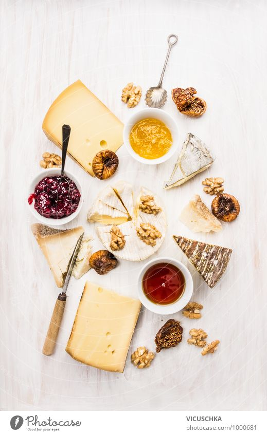 different kinds of cheese with sauce, walnuts and figs Style Design Soft Yellow Brie roquefort camembert Cheese varieties Difference Sauce Bowl Spoon Knives