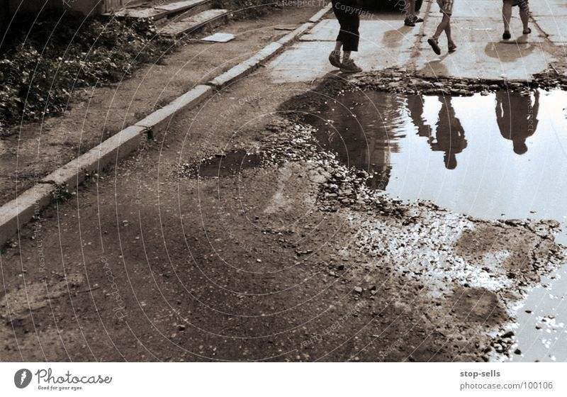 peripheral phenomenon Puddle Child Edge Mirror Reflection Walking Curbside Ukraine Brown Ghetto Youth (Young adults) Dirty Water marginal shape Legs Running