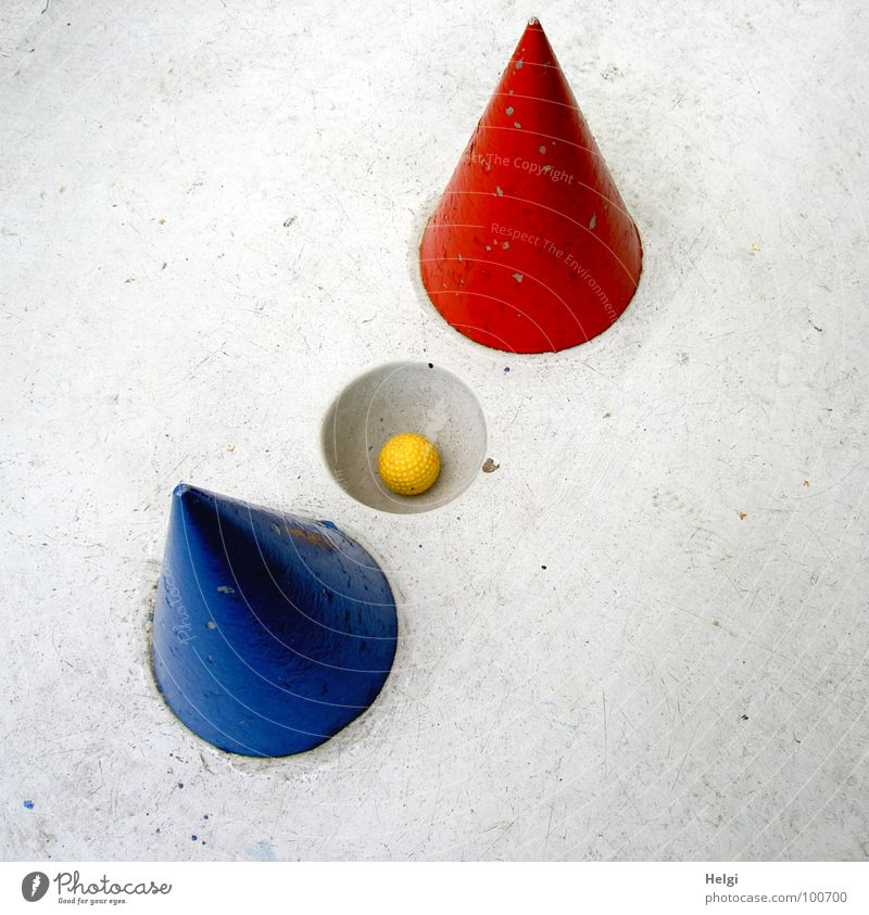 yellow minigolf ball lies in a hole on a grey minigolf course with red and blue cones Mini golf Golf ball Complex Aim Beat Sporting event Playing Summer Lose