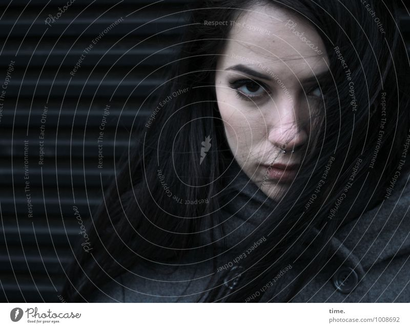 . Feminine Young woman Youth (Young adults) 1 Human being Wall (barrier) Wall (building) Coat Black-haired Long-haired Observe Looking Wait Dark Cold Rebellious