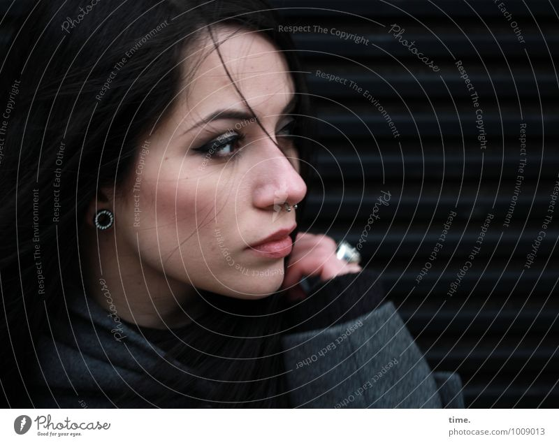 . Feminine Young woman Youth (Young adults) 1 Human being Wall (barrier) Wall (building) Coat Piercing Black-haired Long-haired Observe Rotate Looking Dark