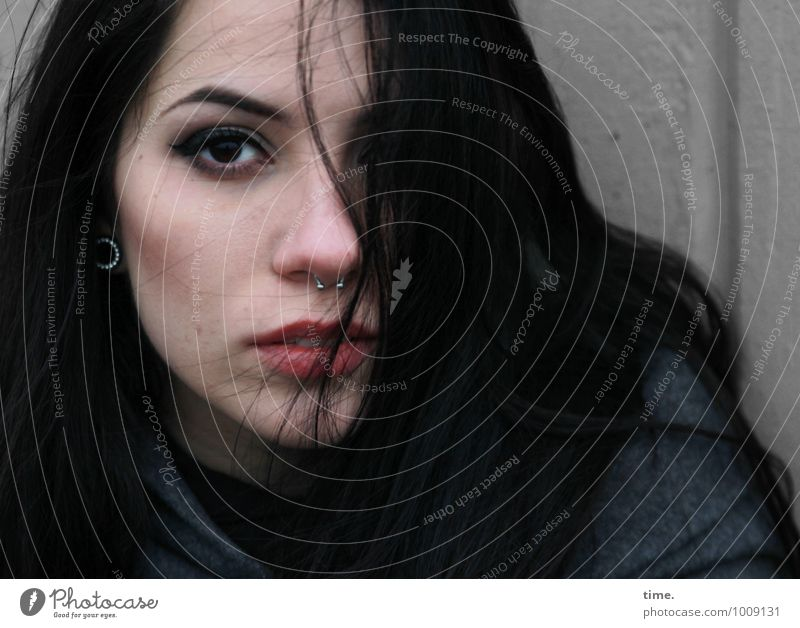 . Feminine Young woman Youth (Young adults) 1 Human being Wall (barrier) Wall (building) Coat Piercing Earring Black-haired Long-haired Observe Think Looking
