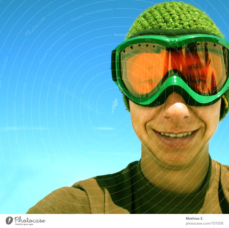 Smile like you mean it Skiing goggles Young man Grinning Cap Snowboarder Man Blue sky Green Portrait photograph Happiness Recklessness Youth (Young adults) Sky