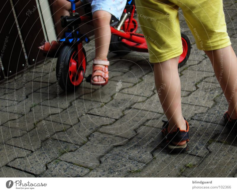 Watch The Children Play Playing Tricycle Driving Red Tread Sandal Stand Kick about Pants Shirt Yellow Footwear Summer Communicate bycicle Seating Sit Wheel