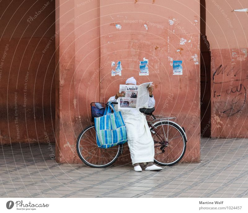 Human being Man Adults Wall (building) Wall (barrier) Facade Masculine Bicycle Wait Reading Serene Africa Newspaper Arabia Morocco Marrakesh