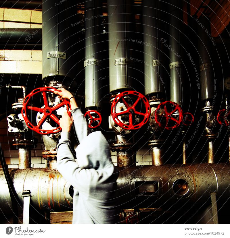Young man closes valve in the combined heat and power plant Industry Industrial plant heating installer heating pump heating engineering heating cellar