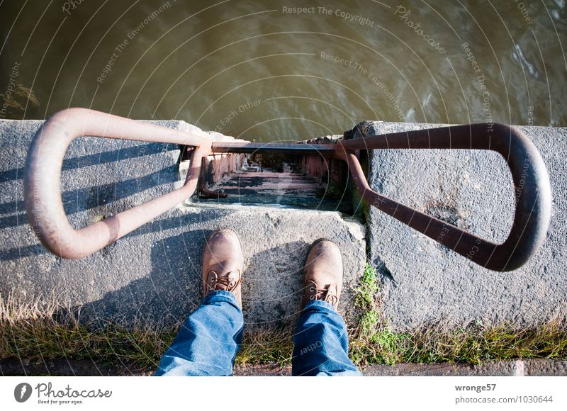 Vertical I Human being Masculine Legs 1 Harbour Wall (barrier) Wall (building) Pants Jeans Footwear Stone Concrete Water Stand Blue Brown Gray Green