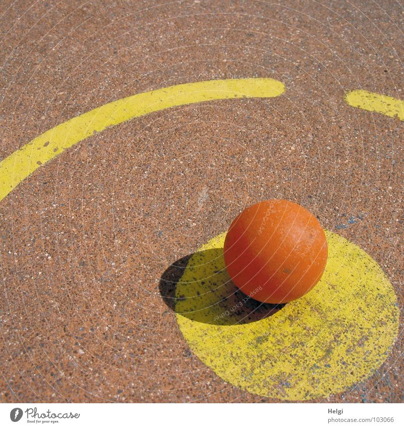 orange minigolf ball is located at the tee-off point on a minigolf course Round Mini golf Tee off Beat Playing Sporting event Yellow Red Concrete Painted Lose