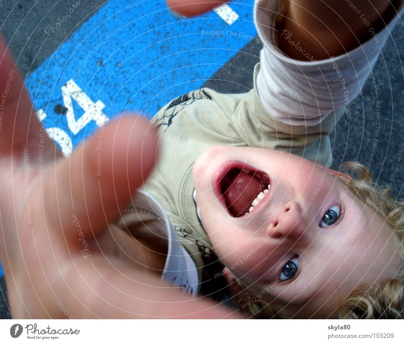 Child Joy Face Eyes Funny Hair and hairstyles Blonde Signs and labeling Mouth Fingers Digits and numbers Joie de vivre (Vitality) T-shirt Asphalt Traffic infrastructure Scream