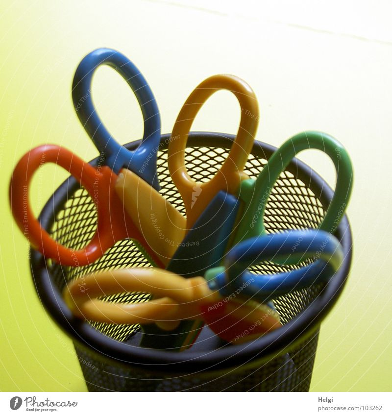 three coloured scissors in a round wire container in front of a yellow background Mug Basket Door handle Cut Edge Vertical Stand Black Reticular Yellow Red