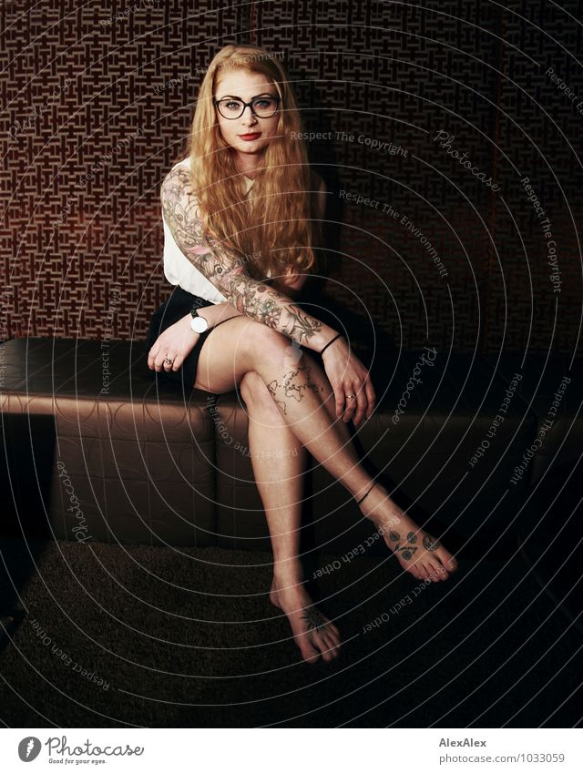 don't wait long Sofa Wallpaper Night life Young woman Youth (Young adults) Face Legs 18 - 30 years Adults T-shirt Skirt Tattooed Eyeglasses Barefoot Red-haired