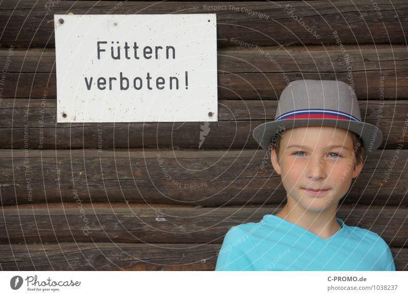 """Boy with hat stands at wooden wall with sign """"Feeding forbidden"""" Human being Masculine Child Boy (child) Infancy 1 8 - 13 years Signage Warning sign Brown"""