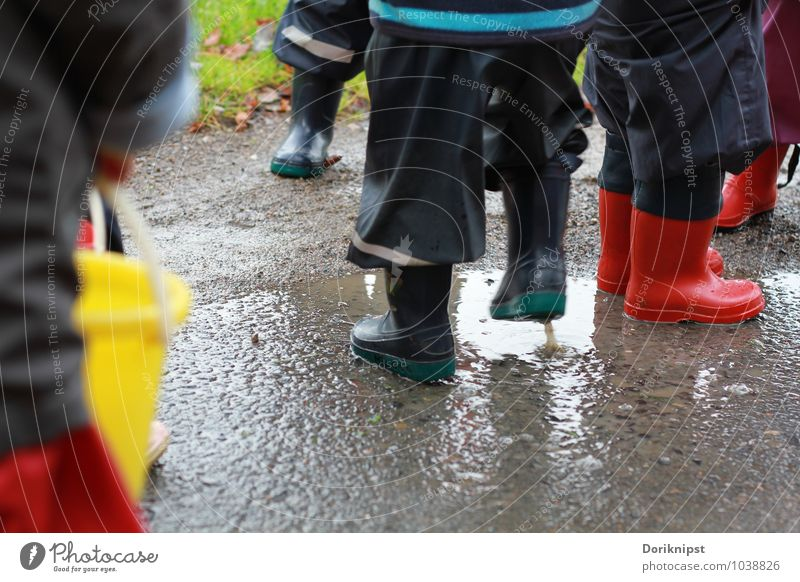 Fun in the rain Joy Playing Kindergarten Human being Toddler Infancy Life Legs Group of children 1 - 3 years Water Autumn Bad weather Village Rain suit