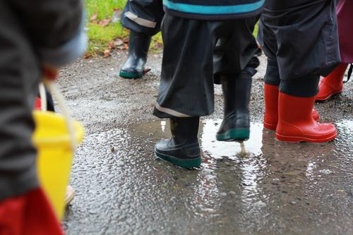 Fun in the rain Joy Playing Kindergarten Human being Toddler Infancy Life Legs Group of children 1 - 3 years Water Autumn Bad weather Village Rain suit