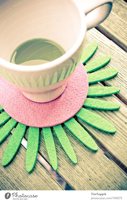 Slightly stocky Cup Café Coffee cup Table Coaster Carry handle Orange juice Wooden table Drinking To enjoy Summer Bleached Balcony Felt Pink Green Gastronomy