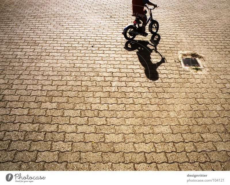 Trial and ... Bicycle Driving Cycling Kiddy bike Child Cobblestones Pedestrian precinct Practice Beginning Playing Wheel Shadow Boy (child) Street