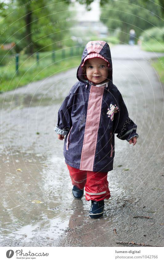 Girl in rainwear Joy Swimming & Bathing Child Toddler 1 Human being 1 - 3 years Park Rubber boots Going Laughter Stand Happiness Wet Infancy Casual clothes
