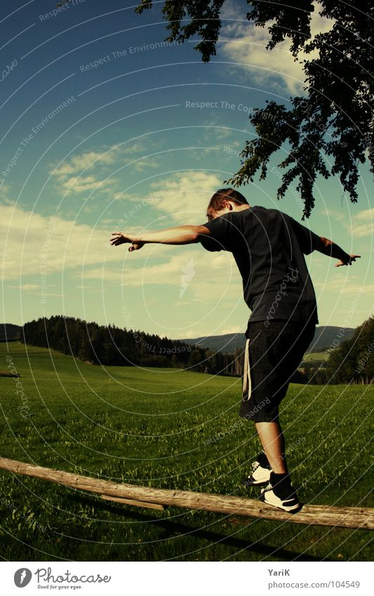 balancing act Balance Contentment Going Tree trunk Wood Meadow Green Man Hill Playing Climbing lock away Pasture Sky Arm Boy (child) Construction site Blue