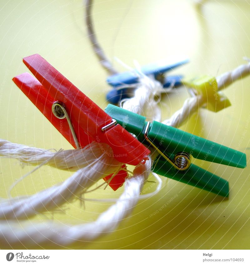 several colorful clothespins clamp on a rope against a yellow background Holder String Packaging tape Clothes peg Wire Attachment To hold on Together