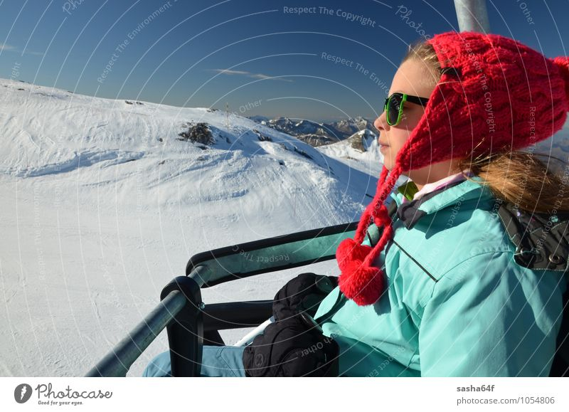 Young girl on chair lift at ski resort Lifestyle Relaxation Vacation & Travel Winter Snow Winter vacation Mountain Chair Sports Skiing Human being Girl Woman