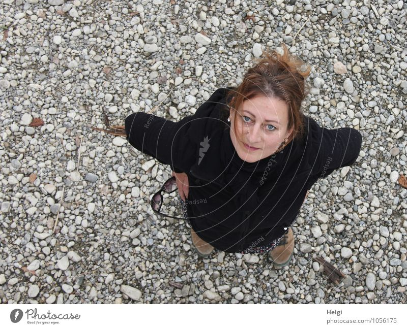Woman with brunette hair pinned up looks friendly upwards into the camera Human being Feminine Adults 1 30 - 45 years Spring Lakeside Jacket Hiking boots