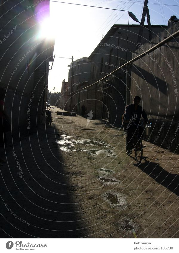 puddles Back-light Puddle Reflection Bicycle Uzbekistan Buchara Asia Alley Village Exterior shot Traffic infrastructure Water Human being dreamed away Tradition