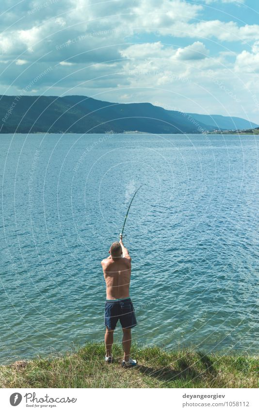 Man on fishing with rod. Mountain lake Human being Sky Nature Vacation & Travel Summer Relaxation Landscape Adults Emotions Sports Lake Watercraft Lifestyle