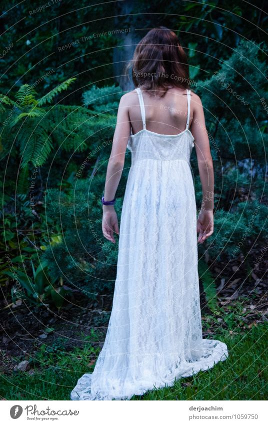Girl in the garden with long white dress. She stands with her back to the camera, in front of her are green bushes and shrubs. Design Harmonious Garden Feminine