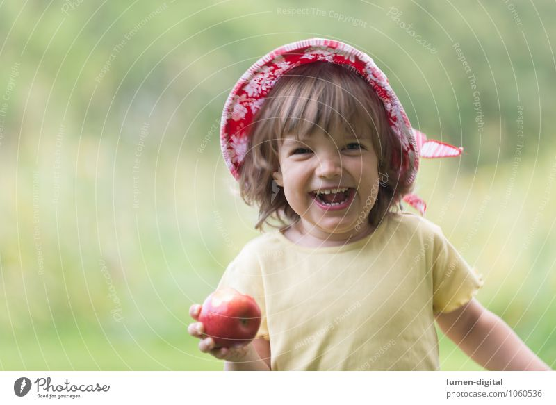 Child is happy with apple fruit apples Nutrition Joy Face Summer Human being Toddler girl 1 - 3 years 3 - 8 years Infancy Hat Eating Laughter Happiness Fresh