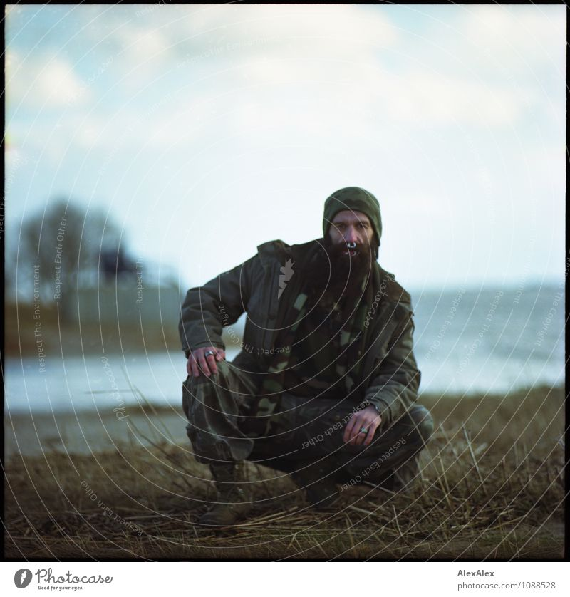 detected Trip Adventure Far-off places Hiking Man Adults 30 - 45 years Nature Landscape Water Grass River bank Camouflage Piercing Cap Beard Observe Crouch