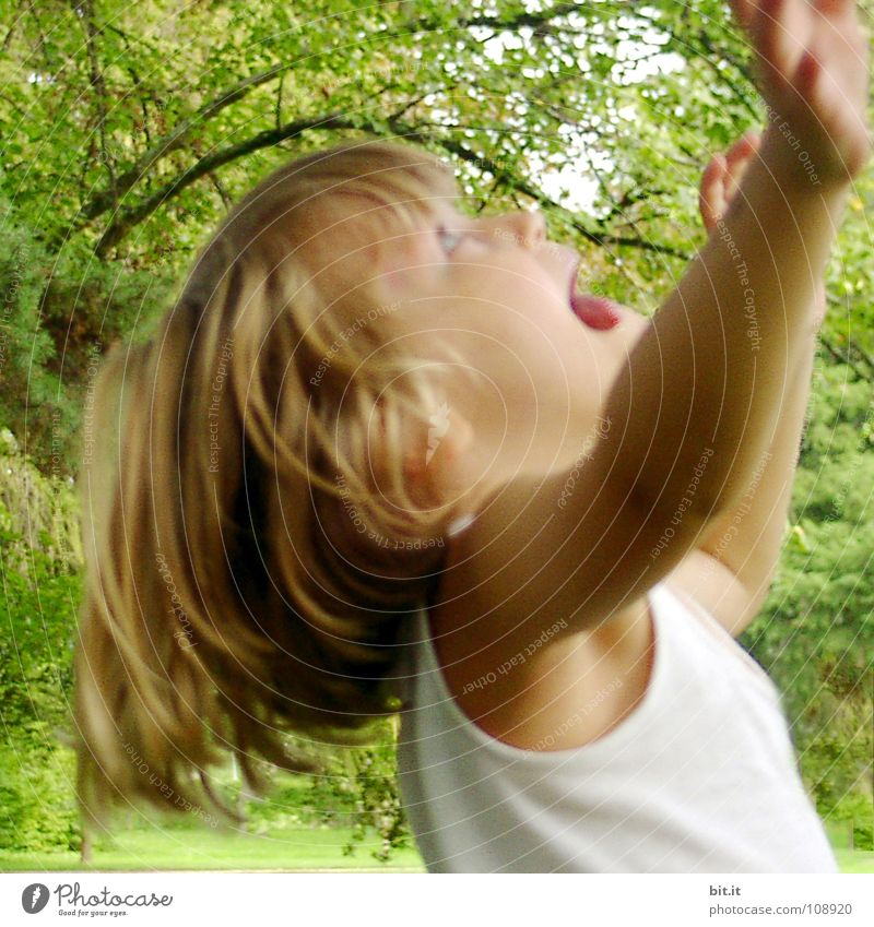 Funny, funny, cheerful, happy, funny blonde girl outside in the garden, looks up and stretches both arms up to the tree. Little joker does nonsense, sticks out her tongue, in nature, in the park under the tree.