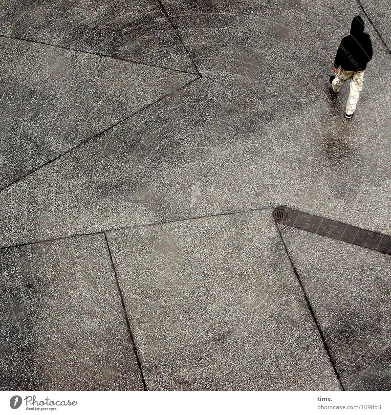 Human being Loneliness Cold Movement Gray Going Masculine Gloomy Wet Corner Asphalt Traffic infrastructure Boredom Backyard Hooded (clothing) Closing time