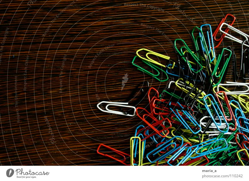 chaos of clamps Paper clip Chaos Muddled Multicoloured Wood Yellow White Reddish black Green Flexible Wire Attachment paperclip chaos Wood grain