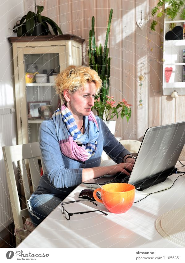 Woman on laptop in home office at home at the table with coffee cup Coffee Cup Hair and hairstyles Life Leisure and hobbies Living or residing Flat (apartment)