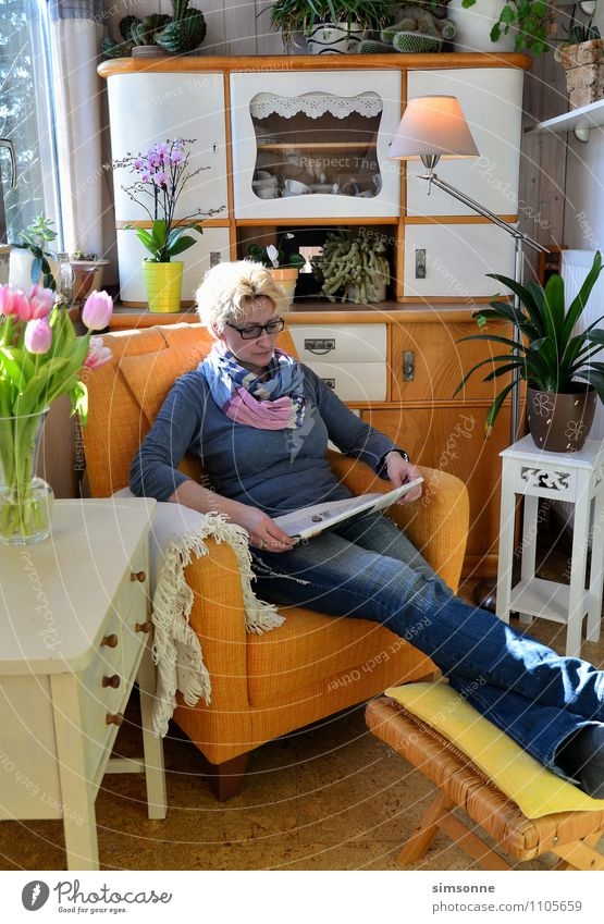 Woman at home reading in an armchair Buffet Brunch Hair and hairstyles Life Leisure and hobbies Reading Sun Living or residing Flat (apartment) Furniture