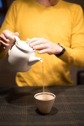 serve the tea Beverage Tea Black tea Pot Mug Tea cup Teapot Joy Man Adults Hand Fingers 1 Human being Table To hold on Elegant Friendliness Brown Yellow Gold