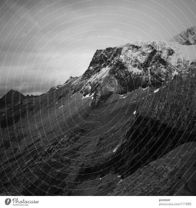 lonely mountain Clouds Black White Vacation & Travel Dangerous Slope Steep Black & white photo Mountain bersch Tall Snow Stone Sky Climbing Threat