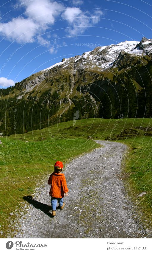on the way Switzerland Child Small Heavenly Clouds Meadow Grass Swing In transit Hiking To go for a walk Boy (child) Baseball cap Idyll Beautiful Pleasant