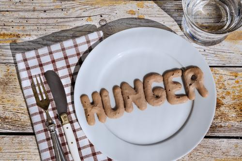 The letters HUNGER on a plate with knife and fork and napkin and a glass of water Nutrition Diet Fasting Appetite Beverage Cold drink Drinking water Plate Glass