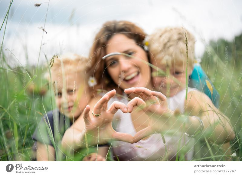 Young mother forms heart with her children in the high grass Joy Leisure and hobbies Playing Trip Freedom Garden Mother's Day Father's Day Parenting Human being
