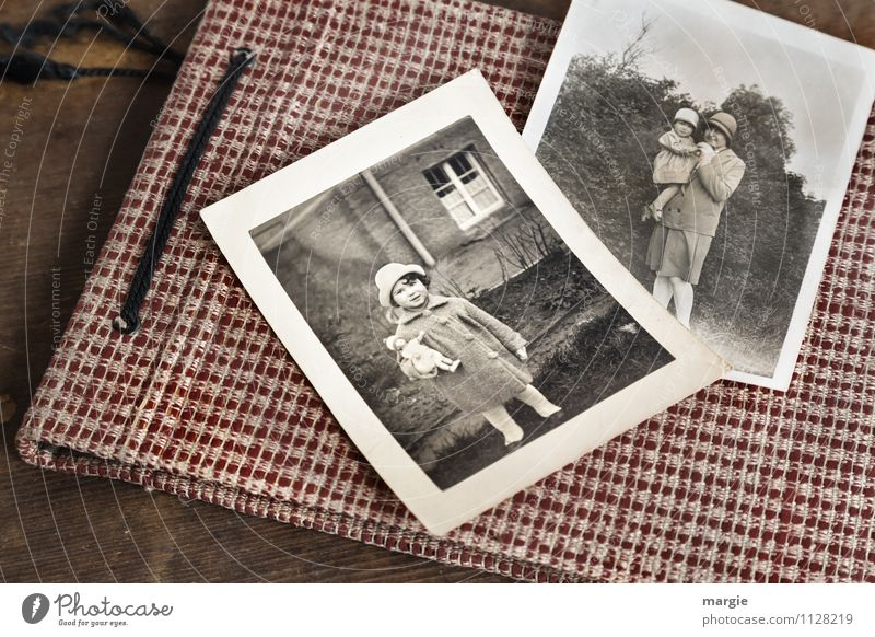 Photo album with old photos, child with doll, mother with child on her arm, both wearing hats Human being Feminine Child Toddler Girl Young woman