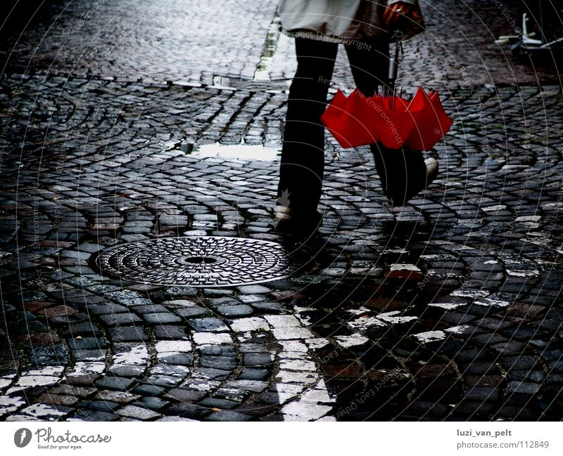 Woman City Red Street Dark Rain Going Wet To go for a walk Umbrella Traffic infrastructure Cobblestones Smoothness Paving stone
