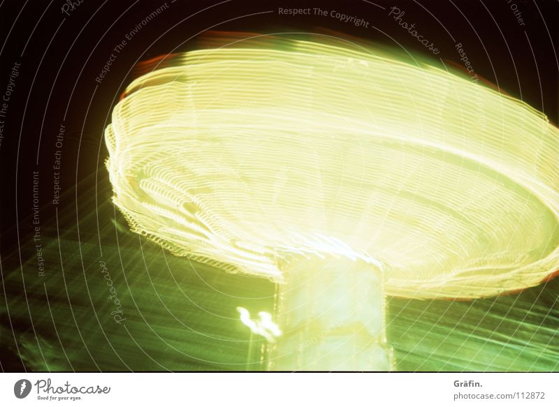 it rotates Fairs & Carnivals Chairoplane Rotate Speed Swirl Light Speed of light Carousel Electric bulb Lamp Strip of light Long exposure To hold on Night Dark