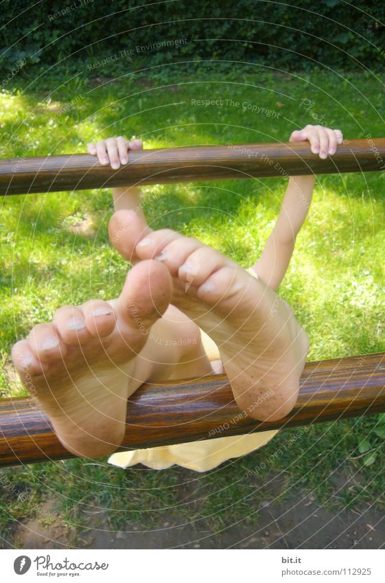 Small child hangs clamped to a wooden bar, outside in the nature. Girl is doing gymnastics on a bar, holding on with her hands and stretching her bare feet upwards. Funny feet, appear oversized and bizarre through perspective.