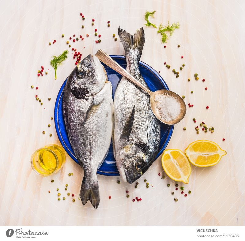 Two Dorado fish on blue plate with oil and lemon Banquet Style Design Healthy Eating Table Kitchen Gourmet delicious Fish Raw Ingredients Herbs and spices