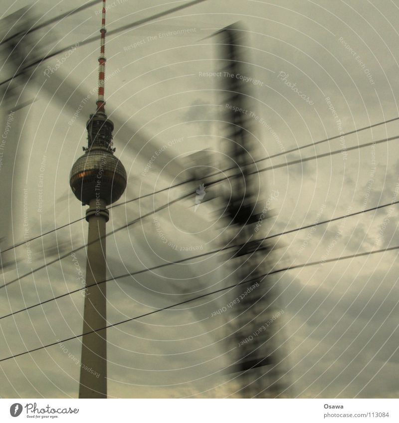 Tower passing by Alexanderplatz Concrete Commuter trains Window Rain Clouds Cloud cover Gray Bad weather Landmark Monument Berlin TV Tower Window pane Glass
