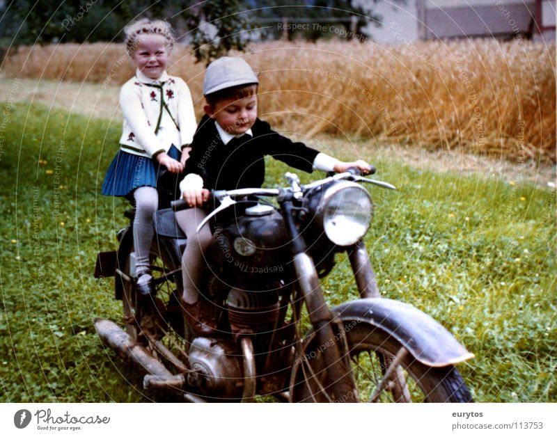 Economic Miracle Years... Colour photo Exterior shot Joy Lamp Child Girl Boy (child) Meadow Field Motorcycle Scooter Hat Green Peace Wheatfield