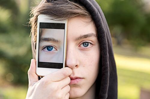 Young man holds a cell phone in front of his eye with a photo of his eye Lifestyle Style Design mobile Technology Telecommunications Human being Masculine