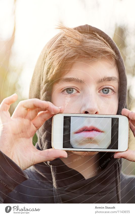 Youngsters hold a mobile phone in front of their mouth with a photo of their mouth on the display Lifestyle Style Design Telecommunications PDA Technology