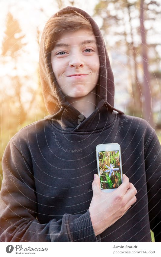 Smiling young man holding a mobile phone with a flower photo for his heart Lifestyle Style Design Telecommunications PDA Technology Human being Masculine